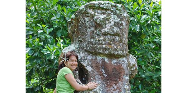 Sandrine Tupai Turquem auprès d'une imposante statue polynésienne.